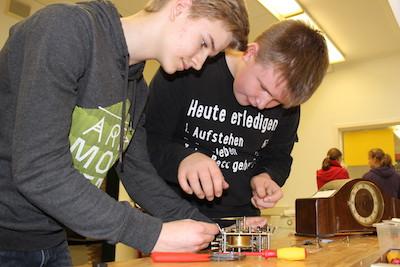 Reparaturen in der Let's MINT-Reparierwerkstatt an der Gesamtschule Ibbenbüren: zwei Schüler beugen sich über eine Uhr