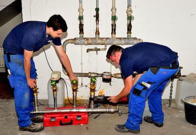 Anlagenmechaniker Sanitär-, Heizungs- und Klimatechnik Sascha Engbert steht mit einem Kollegen vor alten Heizungsrohen und hält eine neue Zuleitung hoch