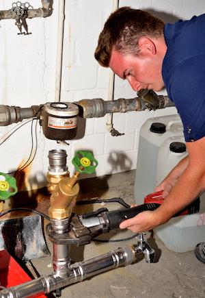 Anlagenmechaniker Sanitär-, Heizungs- und Klimatechnik Sascha Engbert presst mit Spezialwerkzeug eine Leitung für eine Heizungsanlage zusammen
