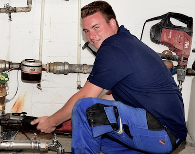 Anlagenmechaniker Sascha Engbert kniet vor den Versorgungsleitungen einer Heizanlagen, denen er ein Rohr auswechselt