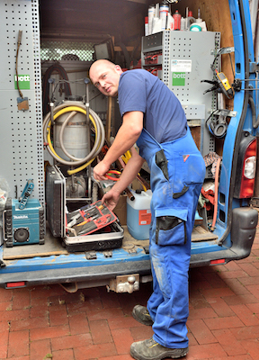 Mitarbeiter von Otte Haustechnik steht am offenen Firmenwagen und lädt Werkzeug aus