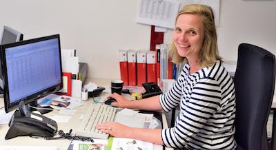 Die Projektleiterin von Otte Haustechnik sitzt am Schreibtisch vor dem PC und lacht in die Kamera