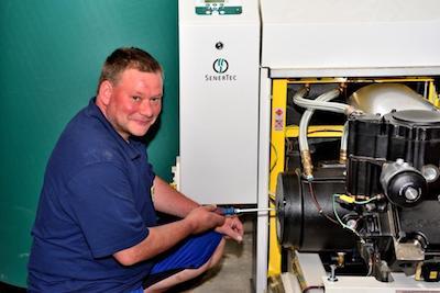 Mitarbeiter von Otte Haustechnik arbeitet an einem Heizkessel und lacht in die Kamera