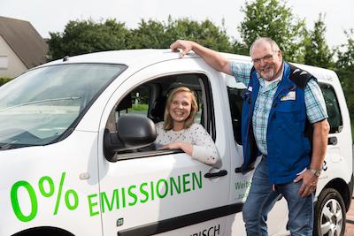 Geschäftsführer Franz-Josef Otte steht an einem Firmenwagen von Otte Haustechnik, in dem seine Tochter, die Projektleiterin Daniela Otte sitzt, beide lachen in die Kamera