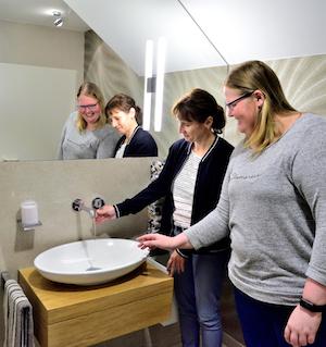 Mitarbeiterin von Otte Haustechnik präsentiert Kundin ein Waschbecken in der Badausstellung
