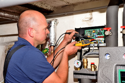 Mitarbeiter von Otte Haustechnik misst mit einem Voltmeter die Spannung einer Heizungsanlage