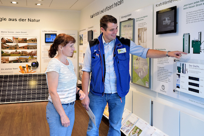Mitarbeiter von Otte Haustechnik erläutert Kundin im Ausstellungsraum verschiedene Alternativen für Heizungsanlagen