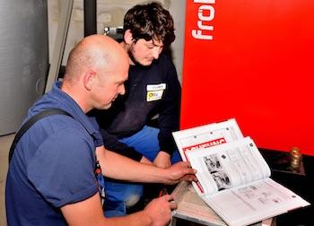 Zwei Mitarbeiter von Otte Haustechnik hocken vor einer Heizung und beraten über die Installation
