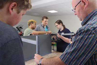 Vier Schüler und ein Reparierexperten schrauben in der Werkstatt die Werkbänke zusammen