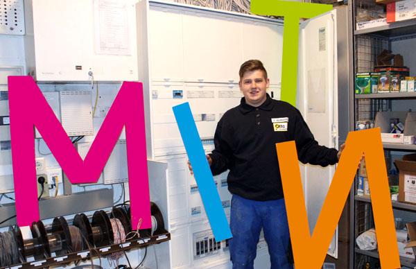 Elektroniker Energie- und Gebäudetechnikg Fabian Selmigkeit posiert mit bunten Buchstaben MINT for Verteilerkasten