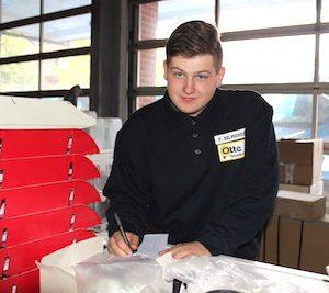 Elektroniker Fabian Selmigkeit steht im Lager an einem Tresen und füllt seinen Stundenzettel aus
