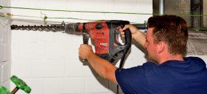 Anlagenmechaniker Sanitär-, Heizungs- und Klimatechnik steht mit schwerer Bohrmaschine vor einer Kellerwand