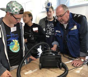Drei Schüler stehen in Reparierwerkstatt um einen Tisch herum und beraten über die Reparatur eines Staubsaugers mit Unterstützung des Reparierexpertens