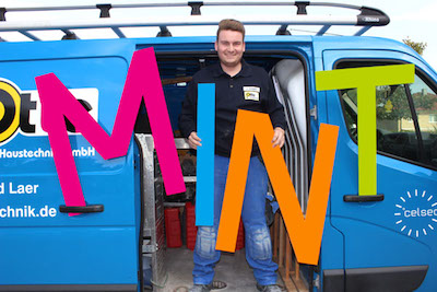 Anlagenmechaniker Sascha Engbert steht in offener Tür des Firmentransporters der mit bunten Buchstaben MINT dekoriert ist