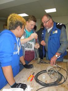 Elektromeiser erklärt zwei Jungen in der Reparierwerkstatt, wie sie ein Elektrokabel verlöten können