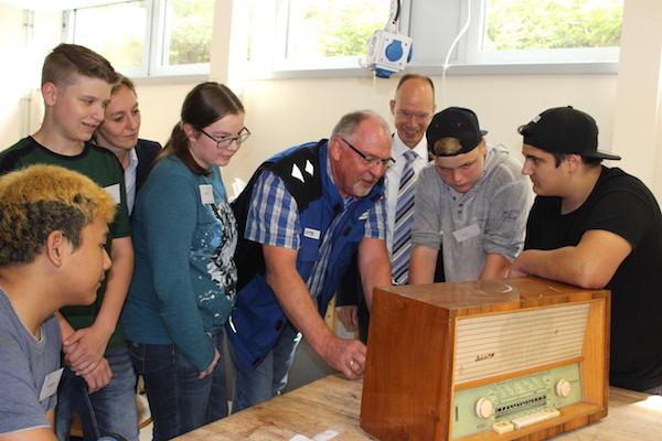 Reparierexperte und Schüler stehen an Werkbank rund um ein altes Radio, Landrat Lübbersmann und Nancy Plaßmann sehen ihnen beim Besuch der innvativen Reparierwerkstätten über die Schulter
