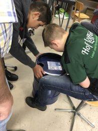 Schüler beugen sich über ein Metallfass, dass sie für die Reparierwerkstatt aufbereiten