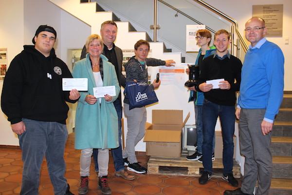 Schüler und Lehrerin haben sich mit Bürgermeistervertreter und Unternehmer zu einem Gruppenfoto aufgestellt vor einer Reparaturbox, die sie zu Abfallvermeidung aufgestellt haben,.
