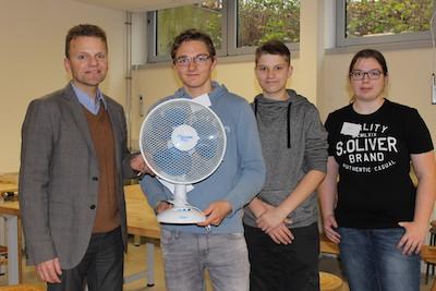 Unternehmer Peter Brinkmann präsentiert gmeinsam mit 2 Schülern und einer Schülerin den erfolgreich reparierten Ventilator