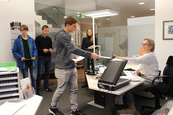 Aktion zur Abfallvermeidung: Schüler übergibt Gemeindemitarbeiterin am Schreibtisch einen Handzettel im Hintergrund stehen weitere Schüler