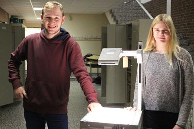 Schülerin und Schüler stehen neben einem erfolgreich reparierten Overheadprojektor