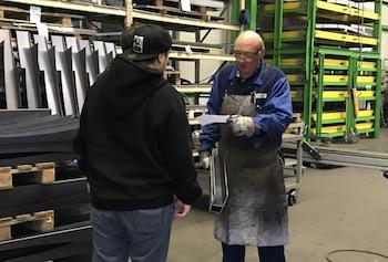 Aktion zur Abfallvermeidung:Schüler übergibt Mitarbeiter in Produktionshalle einen Handzettelgibt