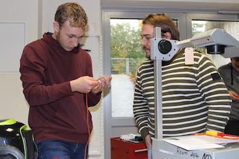 Schüler und Lehrer stehen an einem Overheadprojektor, der Schüler schraubt den Stecker des Projektors auf