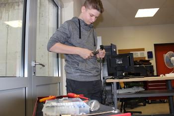 Schüler steht vor einer Werkbank und schraubt eine Steckdose an einem langen schwarzen Verlängerungskabel auf