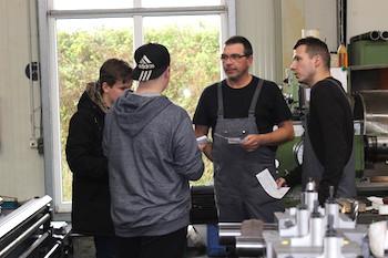 Schüler stellen zwei Mitarbeitern in Produktionshalle ihre Idee vom nachhaltigen Konsum durch Reparieren vor