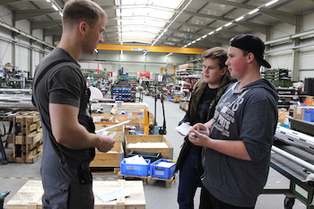 Schüler sprechen mit Mitarbeiter in Produktionshalle, um ihm ihre Idee vom nachhaltigen Konsum durch Reparatur vorzustellen