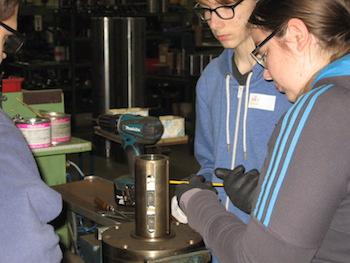 Schüler reparieren unter Anleitung eines Mitarbeiters bei einer Unternehmensexkursion eine Wickelwalze