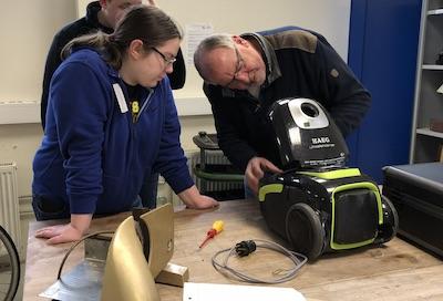 Jede Menge zu reparieren: Schüler untersucht gemeinsam mit Elektromeister einen defekten Staubsauber, der auf einer Werkbank vor ihnen liegt