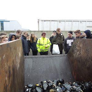 Recyclingexperten und Schüler stehen vor Container mit alten Elektrokleingerätenem Co
