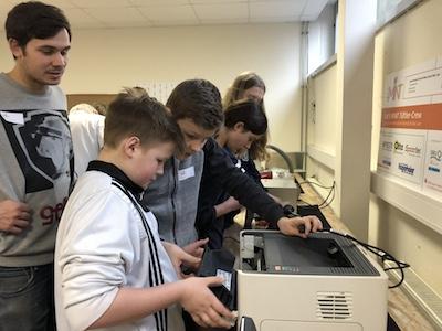 Schüler stehen beim 2. Werkstatttreffen vor Drucker und versuchen den Fehler herauszufinden