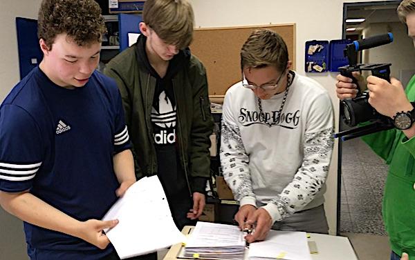 Drei Schüler stehen an einem Tisch und beugen sich über Ordner, in denen sie blättern, dabei werden sie von einem weiteren Schüler gefilmt, von dem nur die Hände sowie die Kamera am Bildrand zu sehen ist.