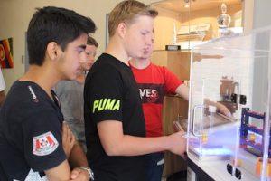 Drei Schüler stehen vor einem Simulator mit dem sie Automatisierungsprozesse an Anlagen ausprobieren können.
