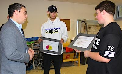 Tiemo Wölken steht links von zwei Schülern, die ihm anhand von Präsentationspappen die Werkstattergebnisse vorstellen.
