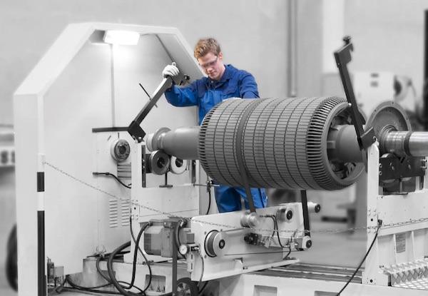 Ein junger Mann mit Schutzbrille steht in blauer Arbeitsschutzkleidung an einer Maschine mit sehr großer Wickelwalze.