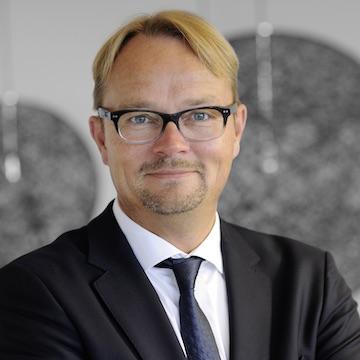 Christoph Sudhoff, Geschäftsführer der Clemens Lammers GmbH&Co. KG steht vor einem grauen Hintergrund und lächelt freundlich in die Kamera.